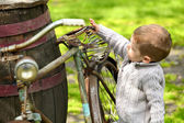 2 years old curious boy walking around the old bike  — Stock Photo