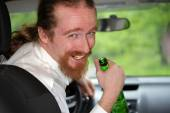 Drunk man in car with a bottle alcohol — Stock fotografie