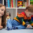 Disappointing girl with her little brother using a digital table — Stock Photo #82165188