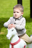 2 years old Baby boy playing with horse — Stock Photo
