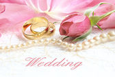 Pair of wedding rings with roses for background image — Stockfoto