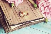 Pair of wedding rings with roses  on wooden background — Stock fotografie