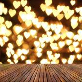Wooden deck table over heart bokeh background. Valentine's day — Stock Photo