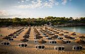 Beach umbrellas at sunset — Stock Photo