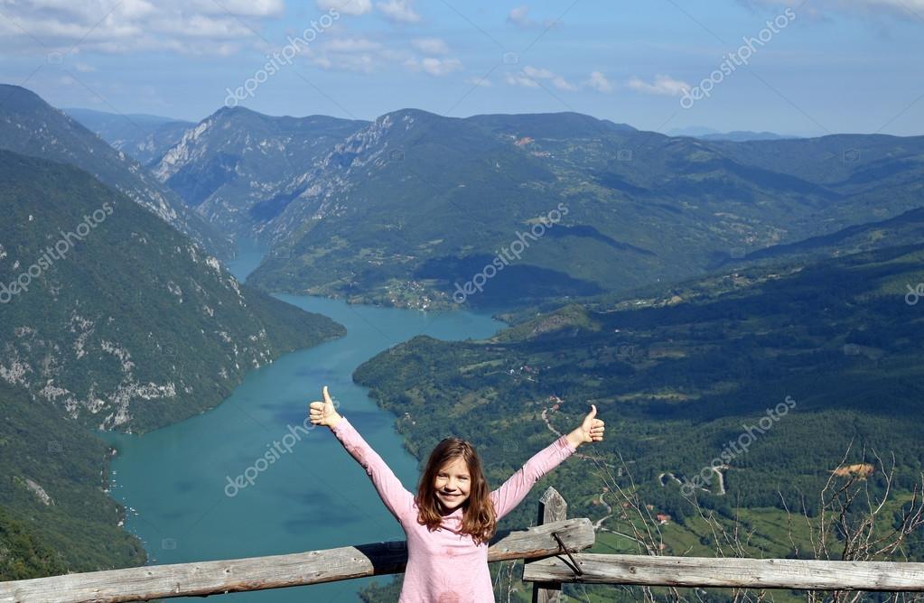 Счастливый маленькая девочка с руками вверх и зонтик в парке осени.