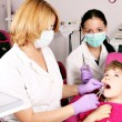 Dentist nurse and little girl patient in dental office — Stock Photo #52518923