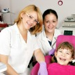 Happy little girl patient with dentist and nurse — Stock Photo #52519041