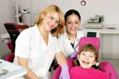 Happy little girl patient with dentist and nurse — Stock Photo