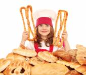 Little girl cook with pastry pretzels and breads — Stock Photo