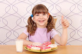Happy little girl with thumb up and donuts for breakfast — Foto Stock