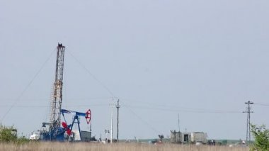 Oil pump jack and land drilling rig — Vídeo de stock