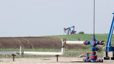 Oil pump jack and pipeline close up — Vídeo de stock