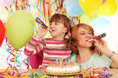 Happy daughter and mother with trumpets and balloons on birthday — Stock Photo