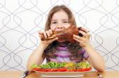 Hungry little girl eating big turkey drumstick  — Stock Photo