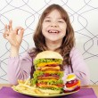 Happy little girl with big hamburger and ok hand sign — Stock Photo #58579695