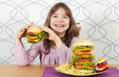 Hungry little girl eat hamburger — Stock Photo