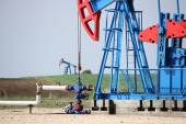 Two oil pump jack and pipeline — Stock Photo