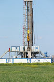 Offshore oil drilling rig on green field — Stock Photo