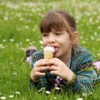 Happy little girl lying on green grass and eat ice cream — Stock Photo #71592363