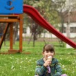 Happy little girl sitting on grass and eat ice cream — Stock Photo #71592399