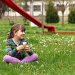 Happy little girl sitting on grass with ice cream — Stock Photo #71592459