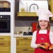 Happy little girl cook with delicious chicken drumstick in kitch — Stock Photo #73756127