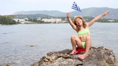 Happy little girl waving with Greek flag on beach Corfu Greece — Stock Video