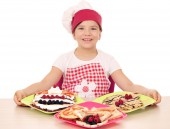 Happy little girl cook with delicious crepes on table — Stock Photo