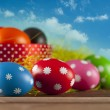 Colored Easter eggs on the grass and blue sky background — Stock Photo #67144255