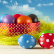 Colored Easter eggs on the grass and blue sky background — Stock Photo #67144409