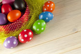 Colored Easter eggs on wooden background — Stock Photo