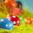 Colored Easter eggs on the grass and blue sky background — Stock Photo #67309581