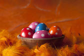 Colored Easter eggs on orange background — Stock Photo