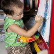 A boy is painting by brush on the easel — Stock Photo #59906693