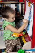 A boy is painting by brush on the easel — Stock Photo
