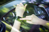 A woman uses smartwatch in the car. — Stock Photo