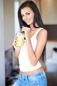 Friendly beautiful woman drinking orange juice — Stock Photo