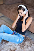 Woman relaxing on the floor listening to music — Stock Photo