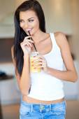 Vivacious woman enjoying a glass of fresh orange — Stock Photo