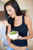 Solbrända friska ung kvinna njuter av en blandad sallad — Stockfoto