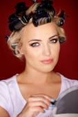Beautiful young blond with her hair in curlers — Stock Photo