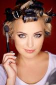 Beauty portrait of a blond wearing curlers — Stock Photo