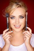 Gorgeous blond woman holding cosmetic brushes — Stock Photo
