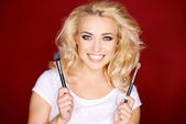 Smiling blond girl holding cosmetic brushes — Stock Photo