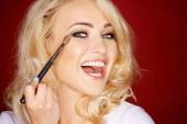 Laughing beautiful woman applying blusher — Stock Photo