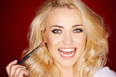 Laughing beautiful woman applying blusher — Стоковое фото