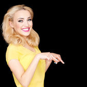 Beautiful blond woman pointing downwards — Stock Photo