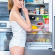 Young woman snacking from her refrigerator — Stock Photo #53079459