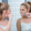 Young woman brushing her teeth in the mirror — Stock Photo #53079605