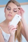Beautiful girl fixing her eye lashes — Stockfoto